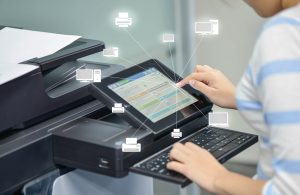 Women using fax machine or printer at office